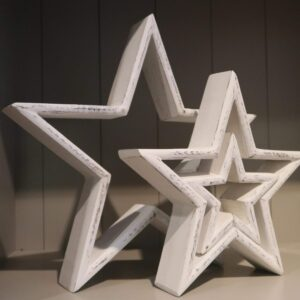 Set of three white wooden stars which vary in size with a distressed paint finish. Can be styled separately or inside one another.