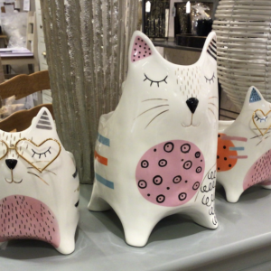 white ceramic pot shaped like a cat with gold and pink accents